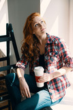 High angle on red haired woman with cup of coffee at home during renovation - 219127534
