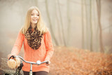 Happy woman with bike bicycle in autumn park. - 219137125