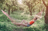 Woman relaxing in hammock in the garden - 219139187