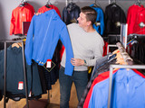 Glad man chooses clothes in shop