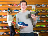 glad athlete chooses sporty clothes and comfortable shoes in the sports shop