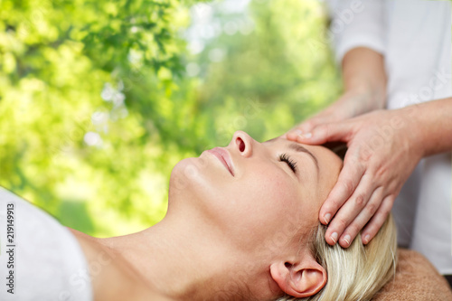Leinwanddruck Bild beauty, wellness and relaxation concept - close up of beautiful young woman lying with closed eyes and having face or head massage in spa over green natural background