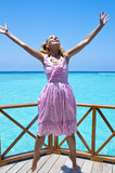 Young beautiful girl jumps in pink sundress on platform of villa on water, Maldives - 219150312