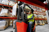 logistic business, shipment and loading concept - loader operating forklift at warehouse