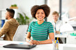 business, education and people concept - happy smiling african american woman with laptop computer sitting at office table - 219155967