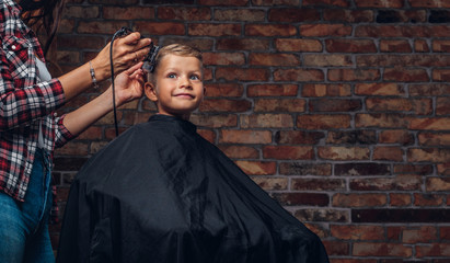 Cute preschooler boy getting haircut. Children hairdresser with trimmer is cutting little boy in a room with loft interior.