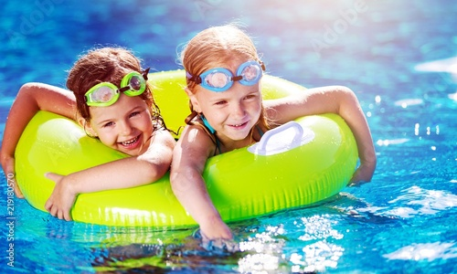 Leinwandbild Motiv Children playing in pool. Two little girls having fun in the