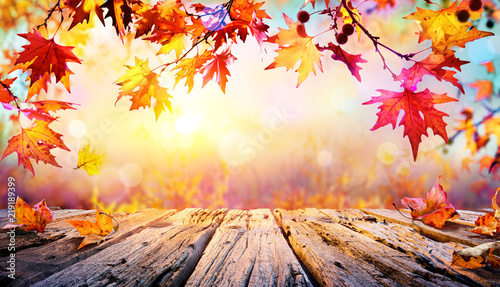 Leinwanddruck Bild Wooden Table With Red Leaves And Autumn Background
