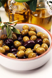 Olives. Bottle virgin olive oil and oil in a bowl with some olives - 219192704