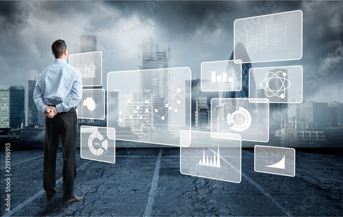 Man looking at user interface over cityscape background © BillionPhotos.com