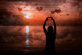Silhouette of woman hands in heart shape with artistic dark red sunset. - 219197764