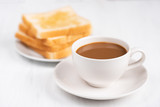 Cup of coffee and sliced bread on white table, breakfast