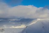 Winter alpine scenery with fresh snow, mist, and beautiful evening light