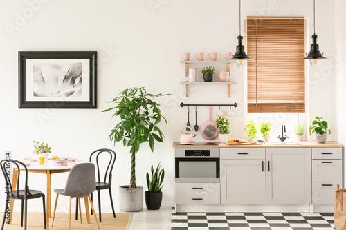 Prawdziwe zdjęcie jasnego wnętrza kuchni z podłogą szachownicy, pastelowe różowe dodatki, świeże rośliny i stół jadalny na dywanie