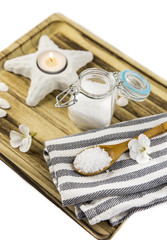 Aromatic sea bath salt on wooden spoon on wooden tray, ocean theme, minimal set spa salon concept, isolated on white. © Helin