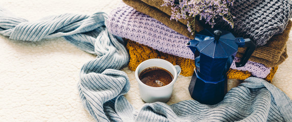 Coffee mug and blue geyser coffee pot on a white coverlet, a stack of knitted clothes and a scarf, long banner © yakovlevadaria