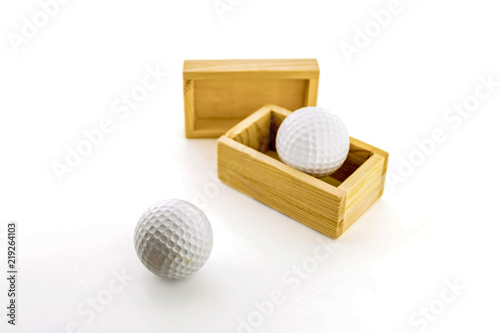 Golf balls in wooden boxes on a white background. - 219264103