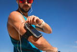 sportsman listening music with earphones and smartphone in armband