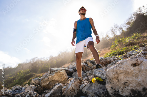bottom view of athletic man standing on rocks with sunlight