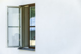 Open window on a white concrete house. Copy space