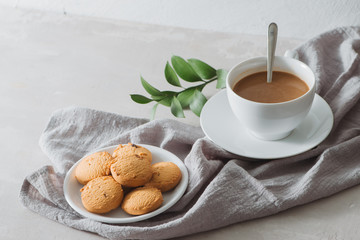 Closeup of coffee with milk in white cup and tasty cookies. Shot on light stone background