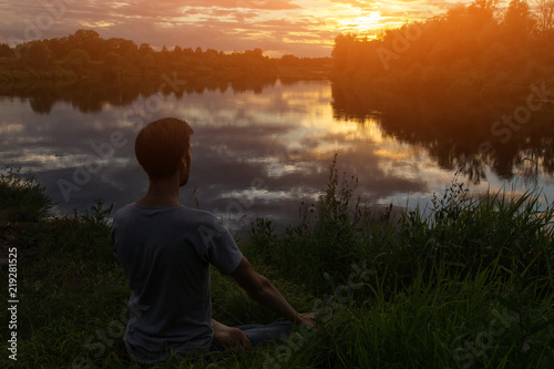 Naklejka Yoga, man in lotus pose meditation, outdoors in nature, copy space