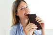 Beautiful young woman biting chocolate bar at home.