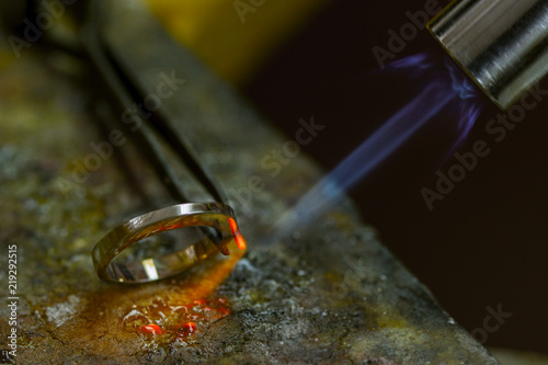 Profession jeweler. Craft jewelery making  in the jeweler's workshop. Soldering process. Closeup. © notistia