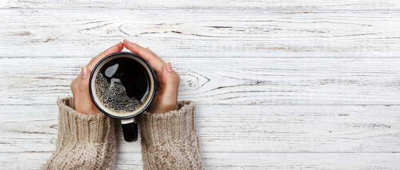 Woman holding cup of hot coffee on rustic wooden table, closeup photo of hands in warm sweater with mug, winter morning concept, top view. Banner © sosiukin