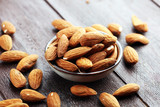 Almonds on a rustic wooden table and almond in bowl. - 219305110