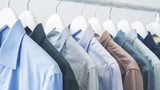 Assorted blue shirts hanging on wooden hangers - 219321159