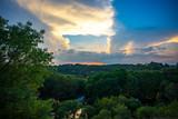 des gros nuages au soleil couchant au dessus d'une forêt