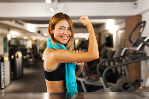 Wall mural happy girl showing muscles in a fitness club