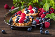 Dessert tarts with raspberries and blueberries on a wooden table. - 219382738