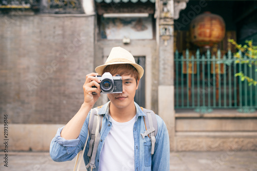 Fototapeta Hobby and travel. Young man with backpack taking photo with his camera on asian street.