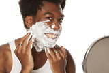 young smiling handsome afro american guy applying shaving foam on white background - 219398336