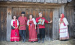 A group of people in russian national costumes stand in a row and pose for the camera against a wooden gate