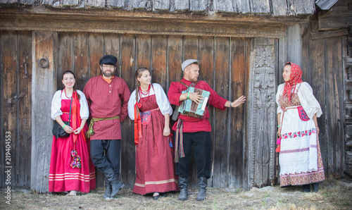 A group of people in russian national costumes stand in a row and pose for the camera against a wooden gate © Barselona Dreams
