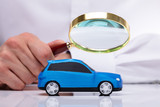 Businessman Holding Magnifying Glass Over Car - 219405966