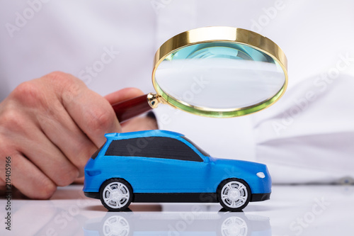 Businessman Holding Magnifying Glass Over Car