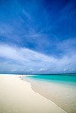 Tropical island in the Indian Ocean. White sand beach, blue sky and a strip of ocean copy space - 219406100