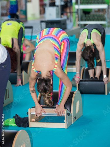 Wall mural Girls in Sportswear doing Fitness Exercises on Little Wooden Bench at Gym