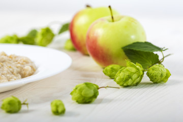 oatmeal porridge abundantly poured creamy melted butter on a white plate among apples and hops