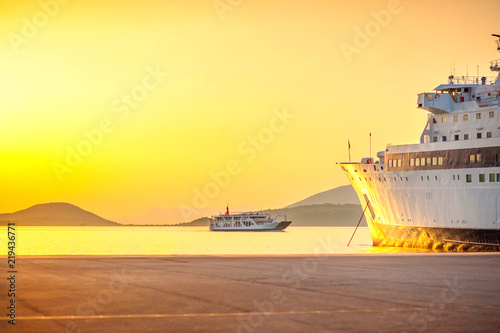 A large cargo ship standing in the port waiting for loading, against the background of a ferry sailing to the port, on a beautiful sunset