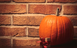 one orange pumpking and gift box on brick wall background. Image with side cornet light