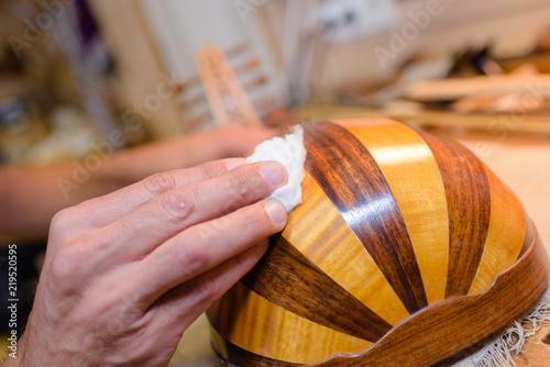 Fototapeta Hands polishing musical instrument