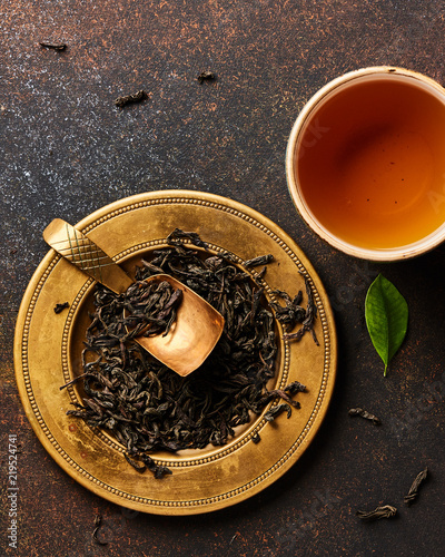 Top view of dried black tea and cup on brown background.
