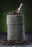 Coffee beans in burlap sack on green background