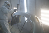 auto mechanic worker painting car in a paint chamber during repair work