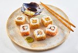 Plate of Uramaki sushi with wasabi and soy sauce - 219571932